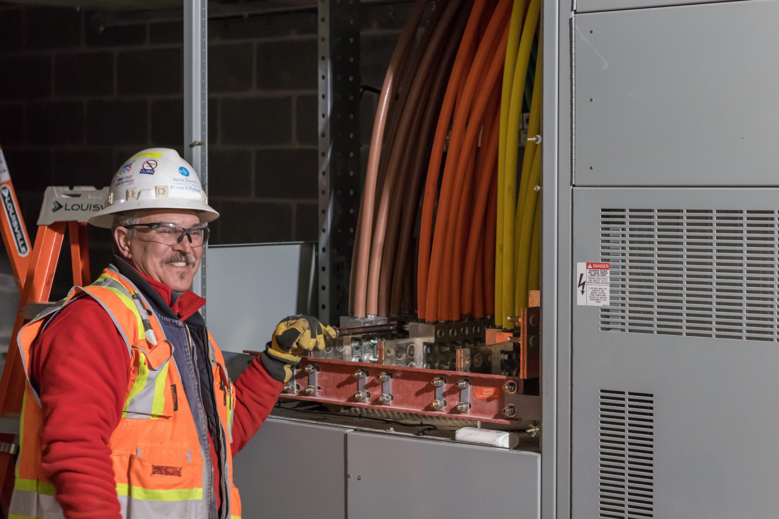 A Helix Electric employee smiles while working